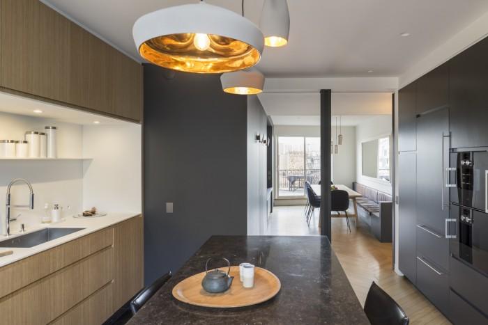Cuisine ouverte sur l'espace salle à manger. Les parois vitrées coulissantes permettent, au gré des habitants, de fermer l'espace de la cuisine tout en conservant la vue, la transparence et le concept du traversant.