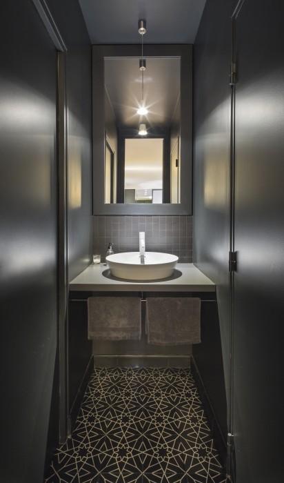Point d'eau pour invités, au total look noir. Le sol est en carreaux de ciment aux motifs noir et blanc.