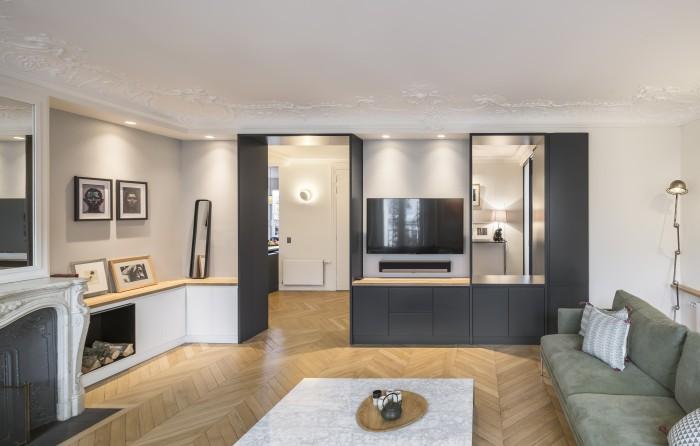 Le meuble sur mesure du salon intègre à la fois le champlat de l'ouverture nouvellement percée et un meuble tv. Ce travail d'ouverture laisse voir l'existence de plusieurs plans et arrières-plans dans l'appartement.