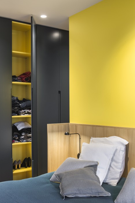 Tête de lit en chêne, adossée contre un mur jaune tournesol. Couleur qui se retrouve à l'intérieur des placard sur mesure, aux poignées en creux.