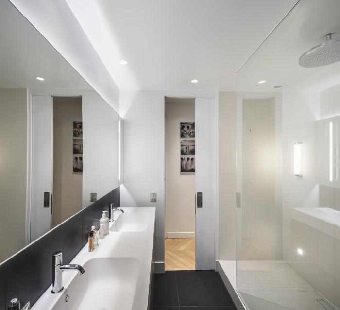 Salle de douche profitant de la lumière naturelle et jouant sur le contraste noir et blanc. Elle est composée d'une porte d'accès à galandage, d'une douche avec double accès et d'une double vasque.