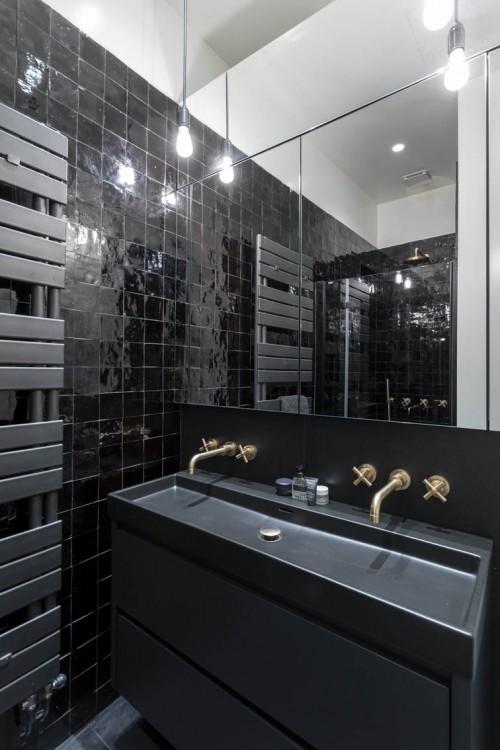 Création d'une nouvelle salle de bain Cette salle de bain, au total look noir, mixe les finitions (brillance des zelliges, robinetterie cuivrée, matité de la vasque…).